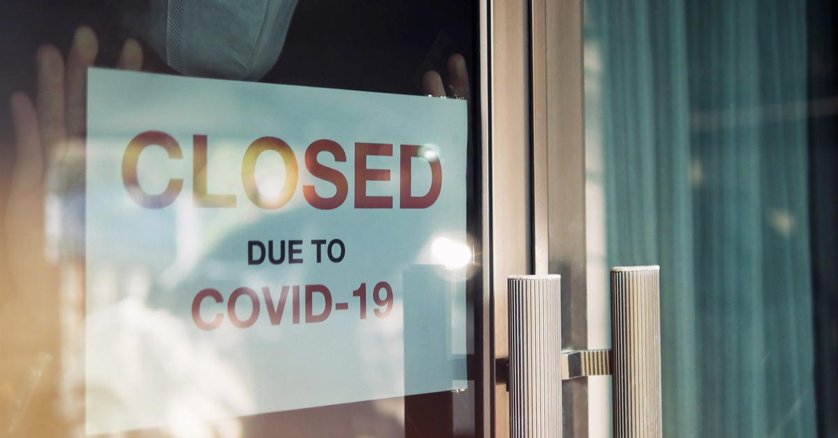 Storefront placing a closed sign due to COVID-19
