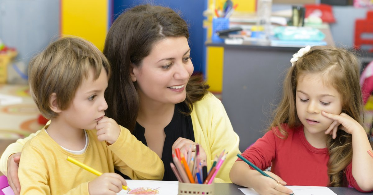 Childcare worker helping two young students with their drawings