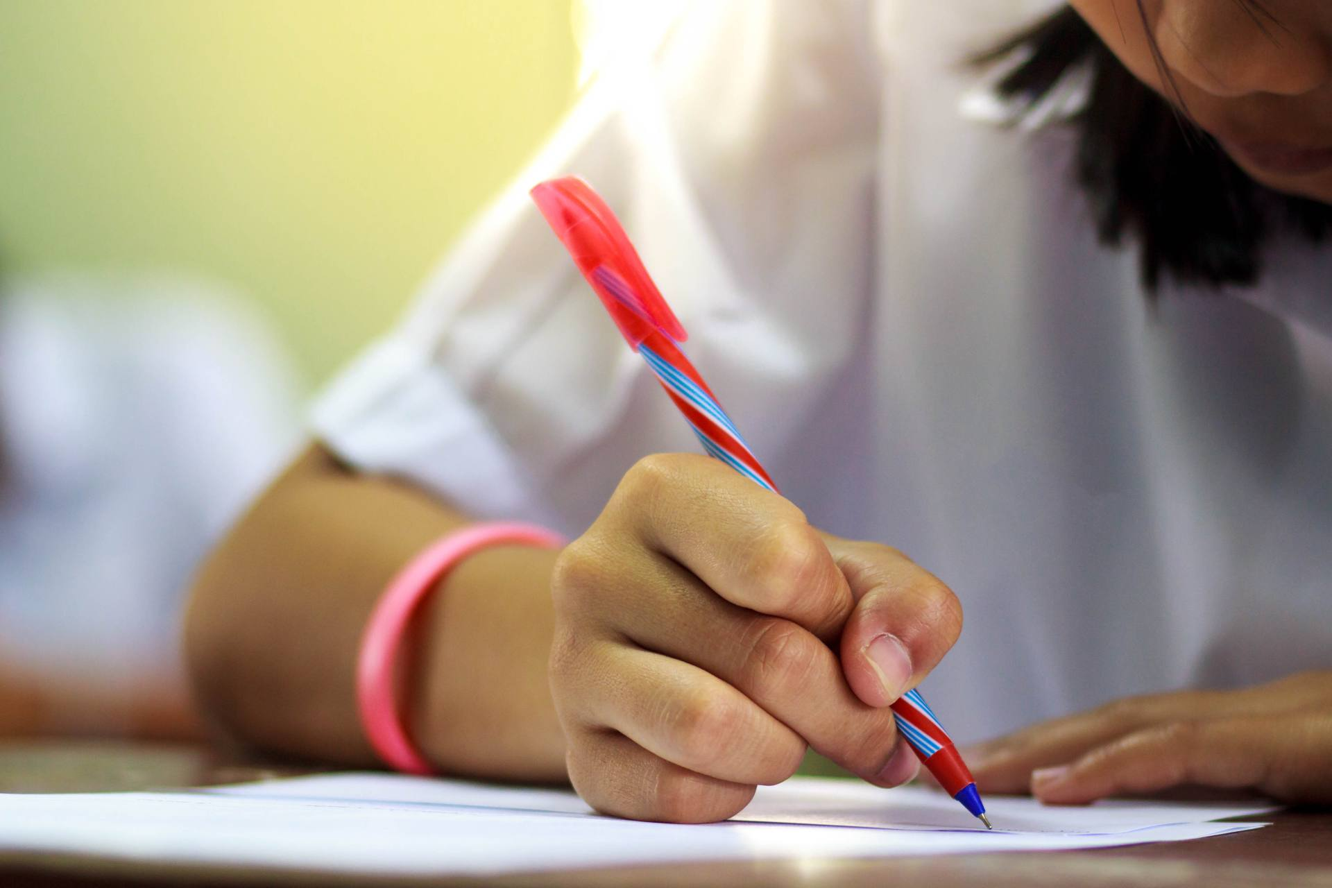 Student with Dysgraphia writing notes in the classroom