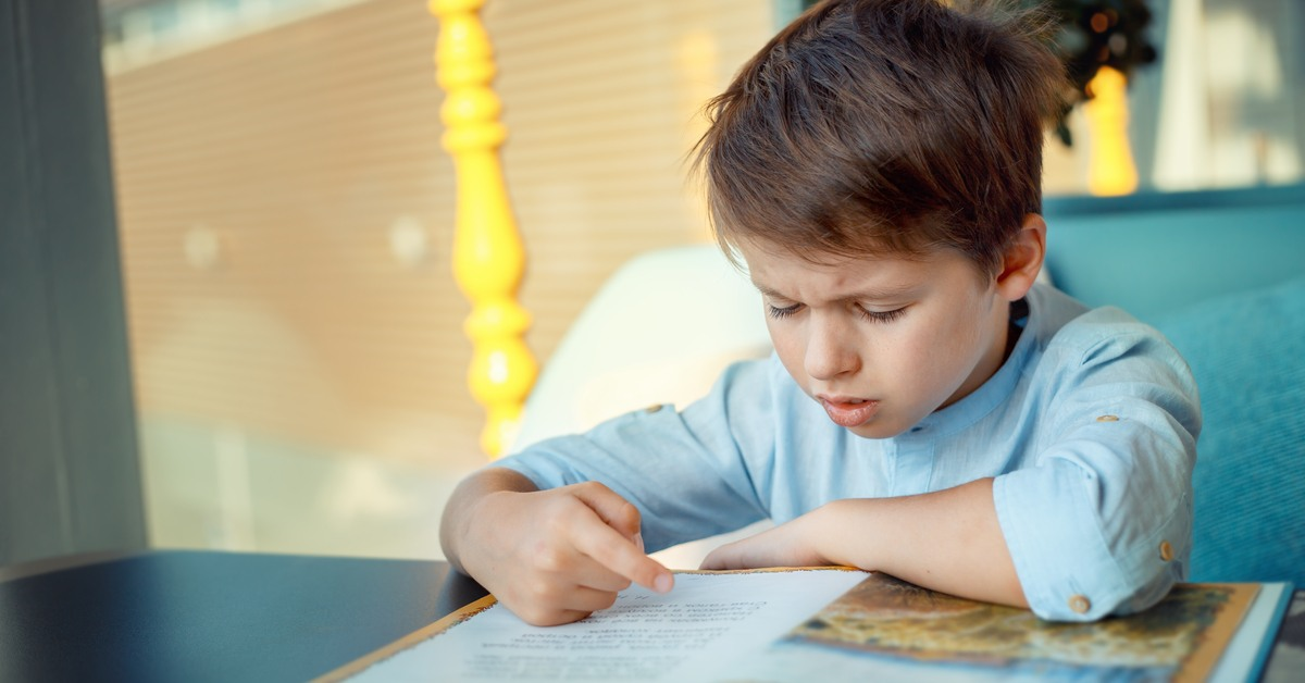 Young student with dyslexia struggling to read through informative book