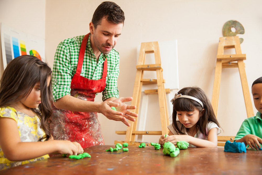 Male childcare worker helping young students construct clay toys