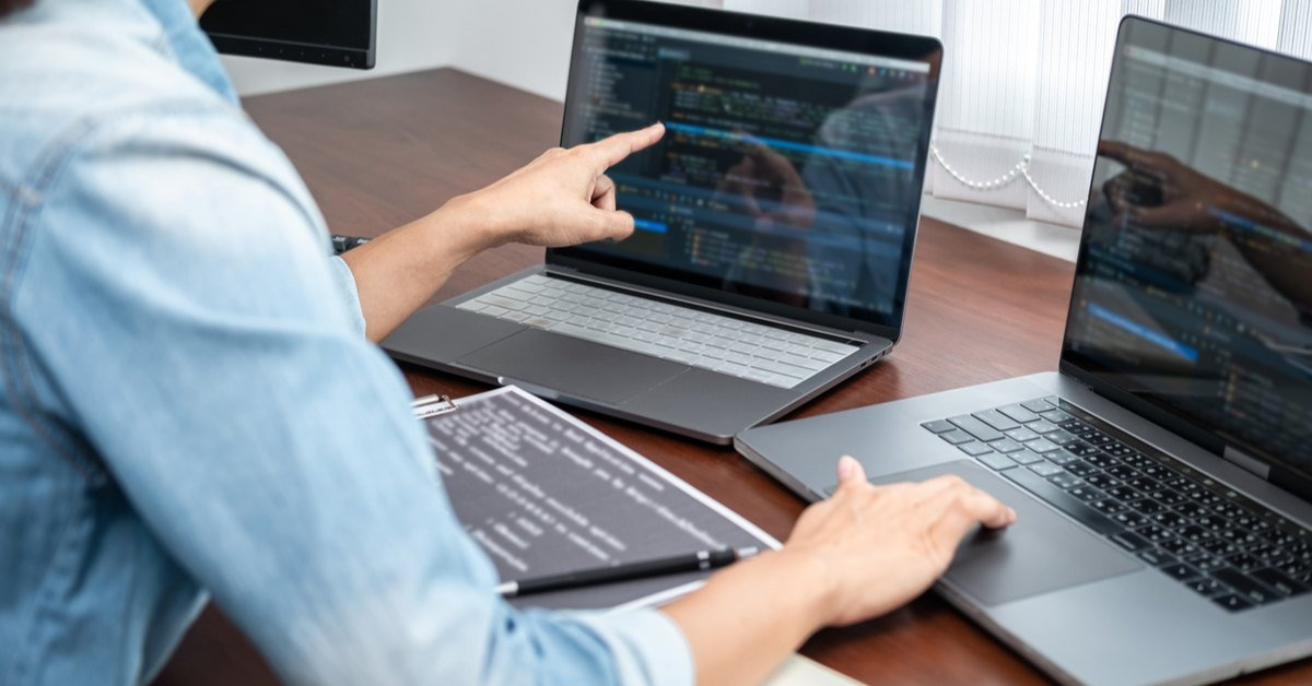 Software and Applications Programmer working on two laptops