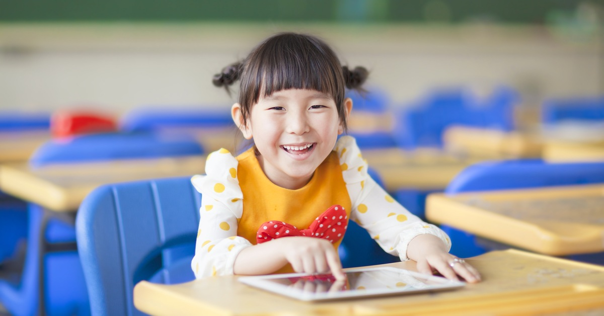 Young student learning in the classroom through technology