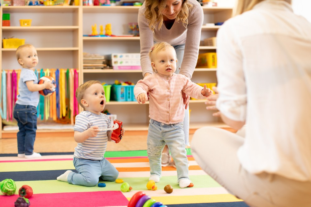 Childcare workers helping toddlers interact with each other
