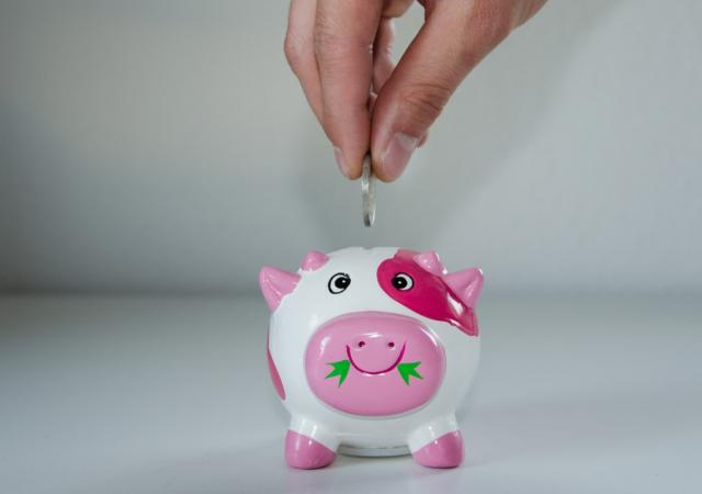 putting money into piggy bank
