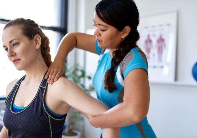 Physiotherapist pushing down on female patients shoulder