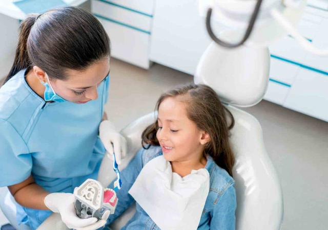 dental assistant showing children good dental care tips