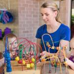 childcare assistant helping children play